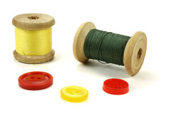 La bobine en bois avec des fils et la couleur se boutonne sur un fond blanc Photographie stock libre de droits