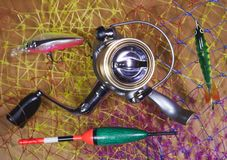 La bobine, le flotteur et les amorces sur un fond de filet de pêche Photographie stock libre de droits