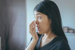 La boca de la cubierta de la mujer y huele su respiración con la mano después de despierta, mún olor foto de archivo
