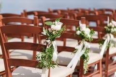 La boda adornó sillas de madera con las flores Foto de archivo