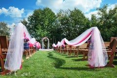 La boda benches con el arco de la flor para la ceremonia al aire libre fotografía de archivo libre de regalías