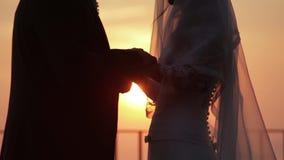 La boda, el novio y la novia llevan a cabo las manos en el fondo del sol naciente sobre el mar almacen de metraje de vídeo