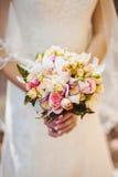 La boda florece el ramo de las rosas en manos de la novia con el vestido blanco en fondo Fotografía de archivo libre de regalías