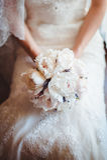 La boda florece el ramo de las rosas en manos de la novia con el vestido blanco en fondo Foto de archivo