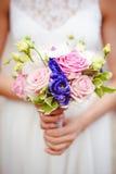 La boda florece el ramo de las rosas en manos de la novia con el vestido blanco en fondo Fotos de archivo libres de regalías