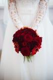 La boda florece el ramo de las rosas en manos de la novia con el vestido blanco en fondo Fotos de archivo