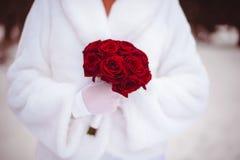 La boda florece el ramo de las rosas en manos de la novia con el vestido blanco en fondo Foto de archivo libre de regalías
