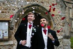 La boda gay, novios sale de la iglesia del pueblo después de estar casado a las sonrisas y al confeti fotos de archivo libres de regalías