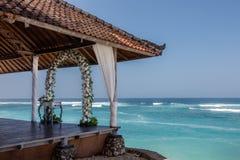 La boda puso - la pérgola de la boda, el arco de la flor y las sillas para las huéspedes cerca del océano, Bali, Indonesia fotografía de archivo