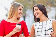 La boisson attrayante de jeunes femmes emportent le café dans la ville d'été Image stock