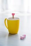 La boisson de chocolat chaud dans la tasse jaune et le coeur forment Photos stock