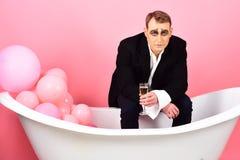 La boisson du moment Mimez l'homme pour célébrer avec le champagne dans le bain L'acteur de comédien apprécient la célébration de photo libre de droits