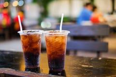 La boisson non alcoolisée avec de la glace et le tube blanc en verre en plastique a placé sur la table Photos stock