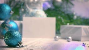 La bola azul del árbol de navidad con el backgroung de las decoraciones del Año Nuevo y de los cristmas empaña vista lateral metrajes