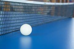 La bola blanca para los tenis de mesa miente en una tabla azul fotos de archivo