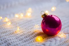La bola carmesí de la Navidad con la guirnalda caliente se enciende en blanco hecha punto Foto de archivo
