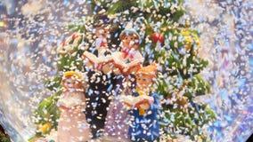 La bola de cristal de la Navidad en nieve con los caracteres miniatura canta villancicos de la Navidad metrajes