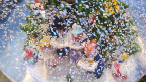 La bola de cristal de la Navidad en nieve con los caracteres miniatura canta villancicos de la Navidad almacen de video