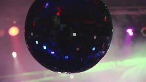 La bola de discoteca giratoria refleja haces coloridos chispeantes de proyectores en club nocturno Humo holidays almacen de video