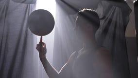 La bola de giro del jugador de básquet en su un finger, haciendo engaña en sitio brumoso con el reflector en fondo almacen de metraje de vídeo