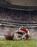 La bola de los jugadores y del casco del fútbol americano en fondo del estadio imágenes de archivo libres de regalías