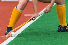 La bola de los pies de la esquina del cortocircuito de la muchacha del hockey da el palillo Fotos de archivo libres de regalías