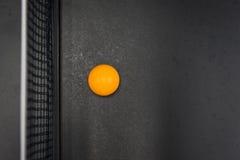 La bola de los tenis de mesa en la tabla negra Fotografía de archivo