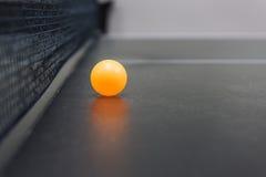 La bola de los tenis de mesa en la tabla negra Foto de archivo