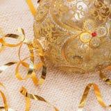 La bola de oro de la Navidad con el vidrio de la decoración de las cintas en una luz hizo punto la bufanda, y nuevo Year& x27; co Imagenes de archivo