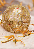 La bola de oro de la Navidad con el vidrio de la decoración de las cintas en una luz hizo punto la bufanda, y nuevo Year& x27; co Fotografía de archivo libre de regalías