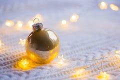 La bola de oro de la Navidad con la guirnalda caliente se enciende en blanco hecha punto Fotografía de archivo