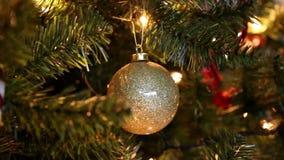 La bola de oro de la Navidad en el árbol con el centelleo enciende el fondo almacen de video