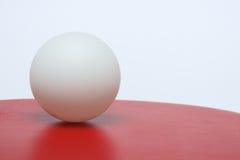 La bola de ping-pong se está colocando en la cara roja del padd Imagen de archivo