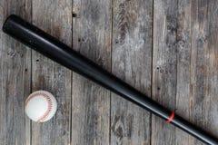 La bola del béisbol del bate de béisbol de madera negro y del cuero blanco miente en los viejos tableros de madera de color oscur fotos de archivo