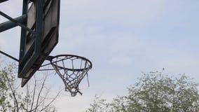 La bola del baloncesto vuela en el anillo metrajes