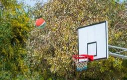 La bola del baloncesto vuela en la meta Imágenes de archivo libres de regalías