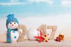 La bola en lugar de otro numera 0 en la cantidad 2017, muñeco de nieve contra el mar Fotos de archivo