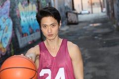 La bola masculina asiática joven de la cesta que lanza con la copia espacia al aire libre Fotos de archivo libres de regalías