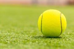 La bola para jugar a tenis está en la hierba verde Foto de archivo