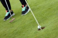 La bola que cae en agujero del golf foto de archivo