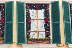 La bola roja de la Navidad adornó ventanas en casa del vintage Imagenes de archivo