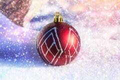 La bola roja del Año Nuevo en la nieve Juguetes de la Navidad Foto de archivo