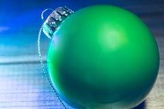 La bola verde de la Navidad en guirnalda azul clara Imagen de archivo libre de regalías