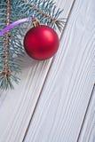 La bola y el pinetree rojos de la Navidad de la estera de la imagen de Copyspace ramifican en wh imagen de archivo