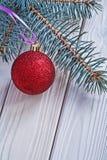 La bola y el pinetree rojos de la Navidad de la estera ramifican en el tablero de madera blanco imagen de archivo libre de regalías