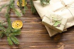 la bolsa de la caja de regalo y de papel de Kraft en la tabla de madera adornó el abeto y la naranja seca Imagen de archivo libre de regalías