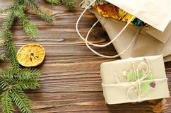 la bolsa de la caja de regalo y de papel de Kraft en la tabla de madera adornó el abeto y la naranja seca Fotos de archivo
