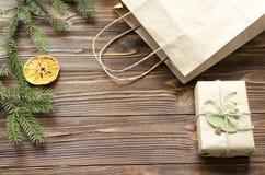 la bolsa de la caja de regalo y de papel de Kraft en la tabla de madera adornó el abeto y la naranja seca Imágenes de archivo libres de regalías