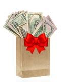 La bolsa de papel con los dólares americanos y el ribon rojo arquean Fotos de archivo libres de regalías