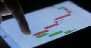 La bolsa y el mercado de acción financian el comercio en gráfico y carta del cojín de la tableta metrajes